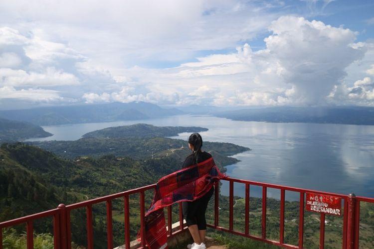 Pengunjung sedang menikmati pemandangan Danau Toba di Huta Ginjang di Kabupaten Tapanuli Utara