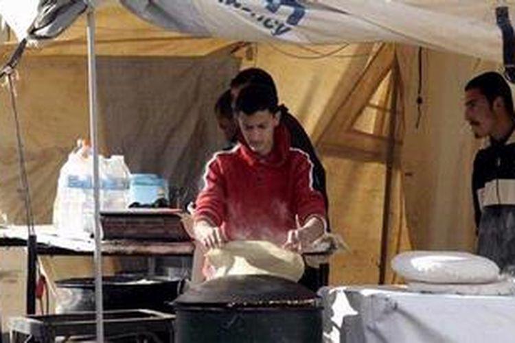 Seorang pengungsi Suriah di kamp pengungsian Zaatari dekat perbatasan dengan Jordania tengah membuat roti. Badan Pangan Dunia (WFP) memperkirakan satu juta warga Suriah kini menderita kelaparan akibat konflik bersenjata yang tak kunjung usai.