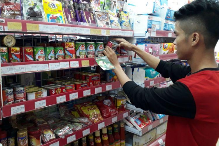 Salah seorang warga terlihat serius melakukan pengecekan salah satu makanan kaleng. Saat ini BPOM telang mengumumkan ada 27 produk makanan kaleng mengandung cacing.
