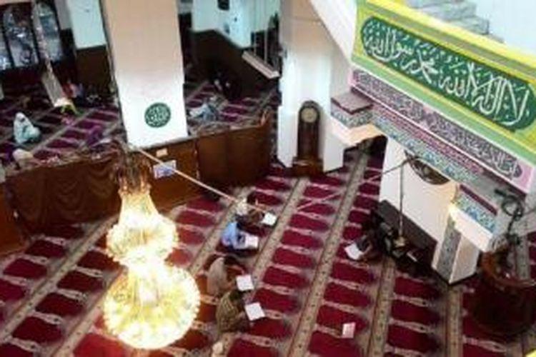 Anggota jemaah Masjid Cut Meutia membaca Al Quran sembari menunggu waktu berbuka puasa, Rabu (8/7). Masjid yang terletak di Kawasan Menteng, Jakarta Pusat, itu dulunya adalah gedung milik pemerintahan kolonial Belanda.