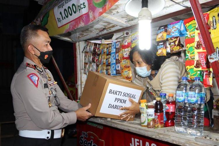 Direktur Ditlantas Polda Lampung, Kombes Raden Romdhon memberikan bantuan paket sembako dan APD kepada pedagang asongan di jalan protokol Bandar Lampung, Kamis (15/7/2021) tengah malam.
