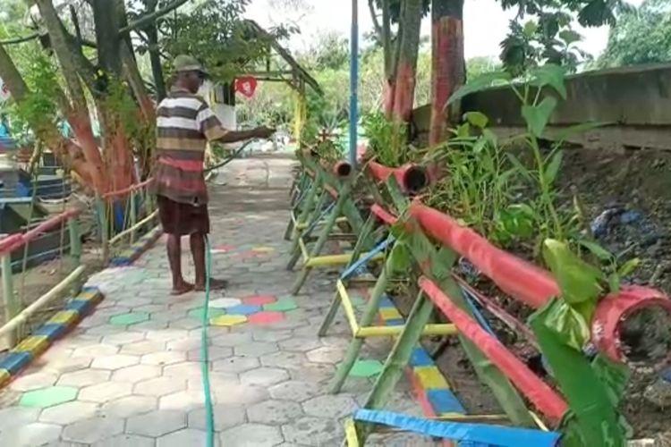 SIRAM—Salah satu pengelola makam Selo, Kelurahan Kanigoro, Kecamatan Kartoharjo, Kota Madiun menyiram sayuran dan tanaman obat-obatan yang ditanam di lahan kosong di area pemakaman.