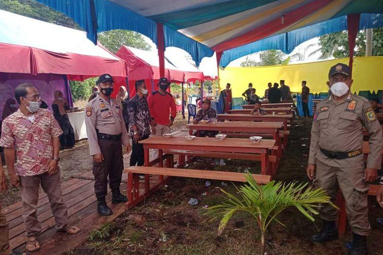 Petugas kepolisian, Satpol PP dan aparat desa saat meminta warga di lokasi pesta pernikahan untuk membubarkan diri dalam rangka mencegah penyebaran Covid-19, di Desa Batang Malas, Kecamatan Tebing Tinggi Barat, Kabupaten Kepulauan Meranti, Riau, Kamis (27/5/2021).