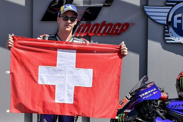 Pebalap Yamaha Fabio Quartararo berpose dengan bendera Swiss sebagai penghormatan untuk pebalap Moto3 Jason Dupasquier, yang meninggal pada usia 19 tahun, karena kecelakaan di kualifikasi Moto3 pada balapan Grand Prix Italia di Mugello pada 30 Mei 2021.