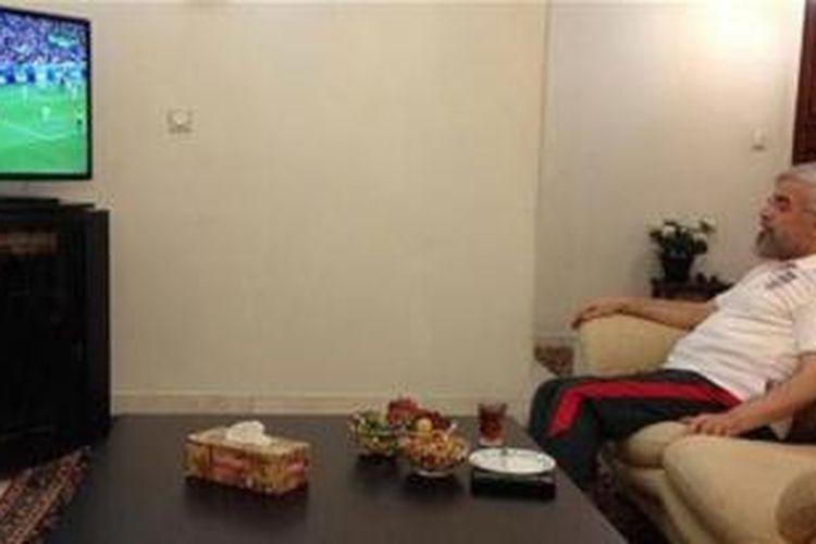 Dalam foto yang tersebar di media sosial ini terlihat Presiden Iran Hassan Rohani serius menyaksikan pertandingan Iran vs Nigeria di televisi sambil mengenakan kaos timnas Iran.