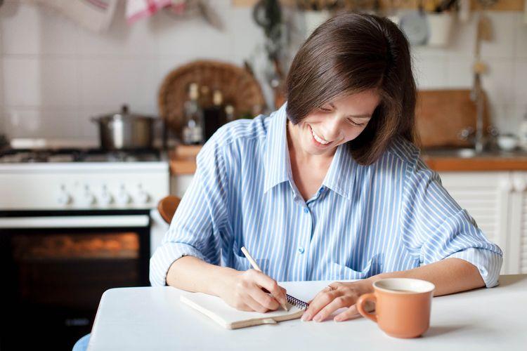 Ilustrasi perempuan menulis jurnal untuk tahun baru.