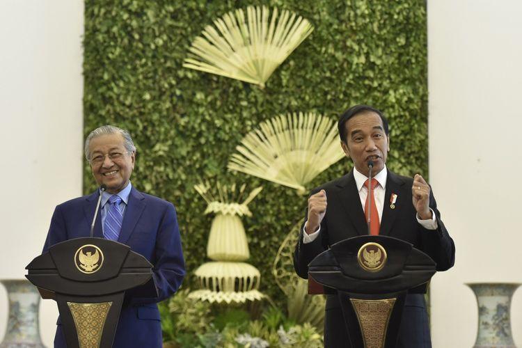 Presiden Joko Widodo (kanan) bersama Perdana Menteri Malaysia Mahathir Mohamad (kiri) menyampaikan keterangan pers usai pertemuan di Istana Bogor, Jawa Barat, Jumat (29/6). Kunjungan kenegaraan tersebut membahas permasalahan perbatasan kedua negara, tenaga kerja, dan sekolah bagi anak Tenaga Kerja Indonesia yang berada di Malaysia. ANTARA FOTO/Puspa Perwitasari/Spt/18
