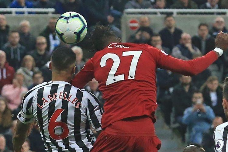 Divock Origi bergerak lebih cepat daripada Jamaal Lascelles dalam menyundul bola pada laga Newcastle United vs Liverpool dalam lanjutan Liga Inggris, 4 Mei 2019.