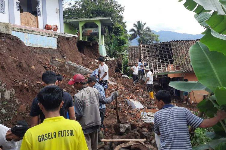 Warga Kampung Gunungsatu Desa Nasol, Kecamatan Cikoneng, Kabupaten Ciamis, sedang bergoting royong membereskan material longsoran tanah yang menimpa rumah dan mengancam masjid amblas, Senin (27/9/2021).