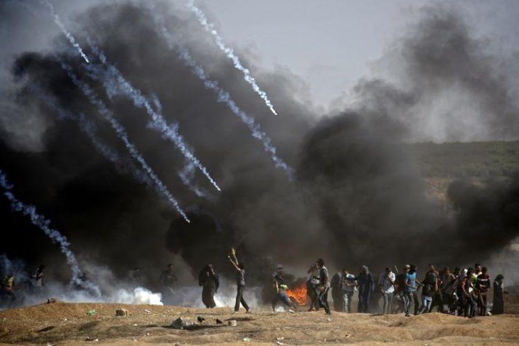 Gas air mata ditembakkan pada massa selama bentrokan dengan pasukan Israel di dekat perbatasan antara jalur Gaza dan Israel, di sebelah timur Kota Gaza pada Senin (14/5/2018). (AFP/Thomas Coex)