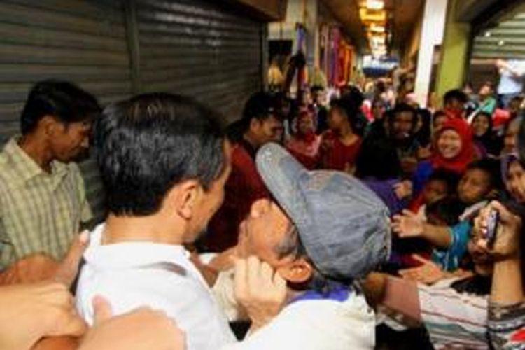 Calon presiden dari PDI Perjuangan Joko Widodo hendak dicium warga di Pasar Kota Gajah, Lampung Tengah, saat blusukan ke tempat tersebut, Sabtu (22/3/2014) siang.