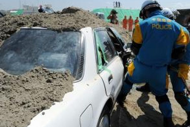 Police officers attempt to open the door of a buried car during a joint disaster prevention drill in Chiba on September 1, 2013.  The joint exercise was held by a coalition of nine regional and local governments around the Tokyo area.