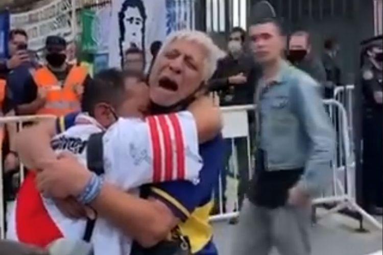 Terlihat ada dua fans sepak bola Argentina, satu pendukung Boca Juniors dan satu lagi River Plate, yang berpelukan dalam isak tangis di luar tempat persemayaman akhir Diego Armando Maradona di Casa Rosada, Buenos Aires, pada Kamis (26/11/2020).