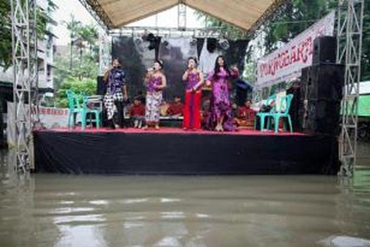 Penyanyi campursari menghibur tamu undangan resepsi pernikahan yang lokasinya terendam banjir di Rumah Susun Bumi Cengkareng Indah, Jakarta Barat, Minggu (1/2). Hujan yang mengguyur kawasan Jakarta dan sekitarnya sepanjang hari menyebabkan sejumlah kawasan tergenang dan banjir.