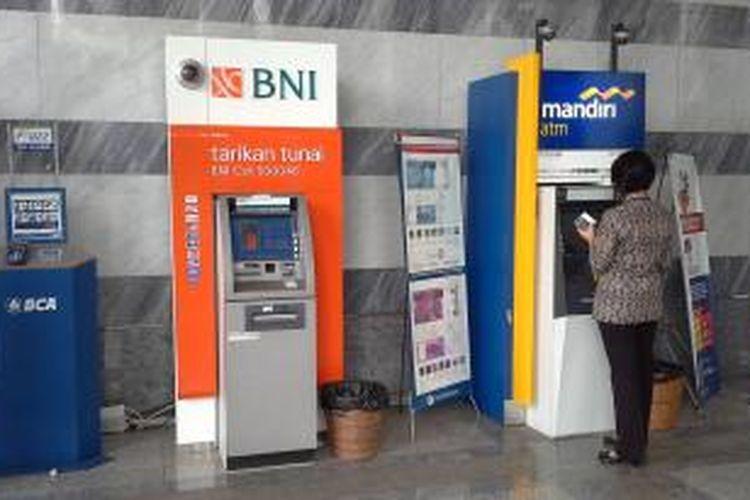 Nasabah melakukan transaksi dengan mesin ATM.