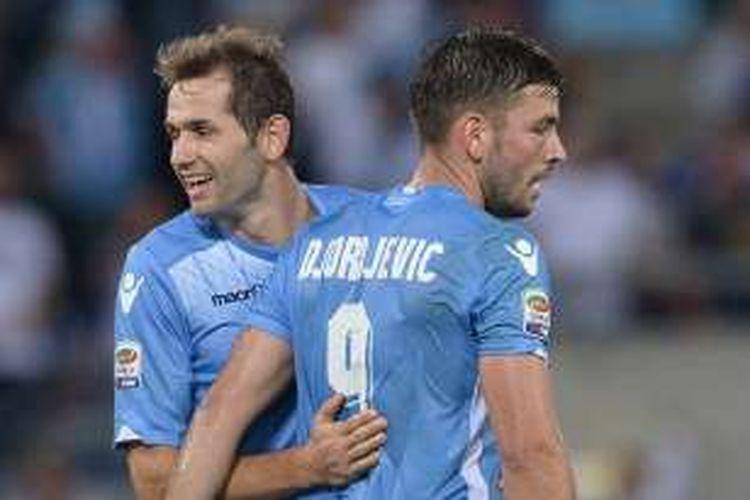 Penyerang Lazio asal Serbia, Filip Djordjevic (kanan), melakukan selebrasi bersama rekannya yang merupakan gelandang asal Bosnia-Herzegovina, Senad Lulic, usai mencetak gol ke gawang Frosinone dalam pertandingan Serie A di Stadion Olimpico pada 4 Oktober 2015.