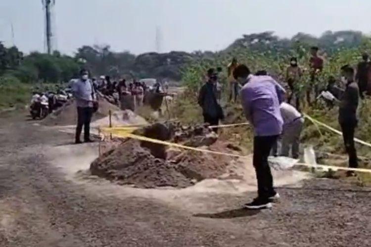 Polisi saat melakukan olah TKP di lokasi penemuan mayat wanita terbungkus karpet merah dan terkubur dalam pasir