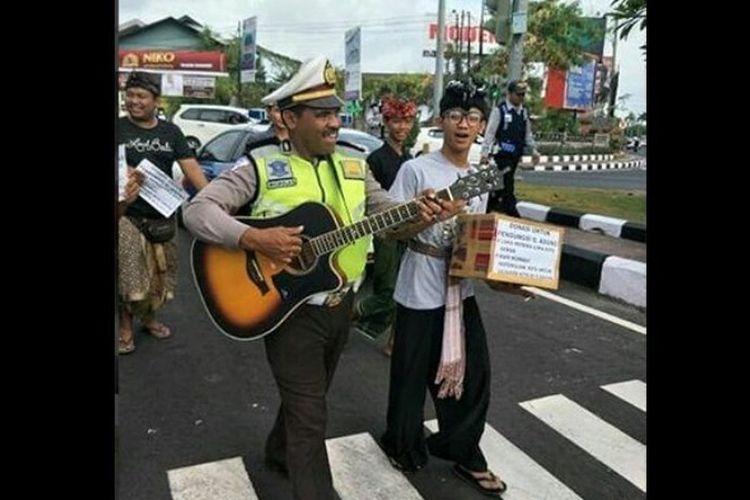 AKP Niko Ruing ketika membantu para relawan mengumpulkan dana di Sunset Road, Kuta, Badung, Bali.