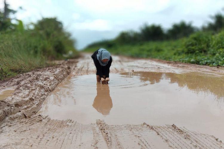 Kondisi jalan rusak yang dijadikan tempat obyek foto model di Kecamatan Pulau Rimau,Kabupaten Banyuasin, Sumatera Selatan.