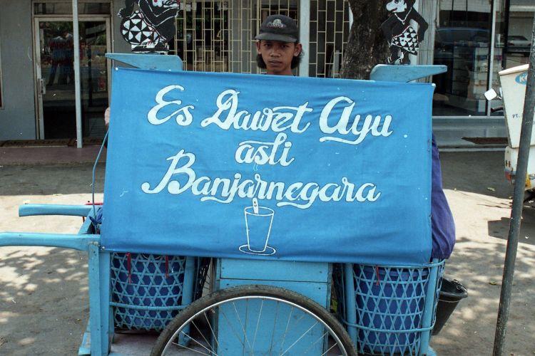 ES DAWET GARENG DAN SEMAR - Penjaja Es Dawet Ayu tengah melayani pembeli di sebuah tepi jalan di Jakarta. Minuman jajanan khas dari daerah Banjarnegara, Jawa Tengah ini dijajakan dengan cara khas, yakni memakai pikulan berhias figur Semar dan Gareng yang ditenggerkan di atas gerobak dorong. Konon, ukiran kayu kedua tokoh punakawan dalam pewayangan ini bermakna simbolis. Gareng adalah simbol penjual, sementara Semar melambangkan pembeli.