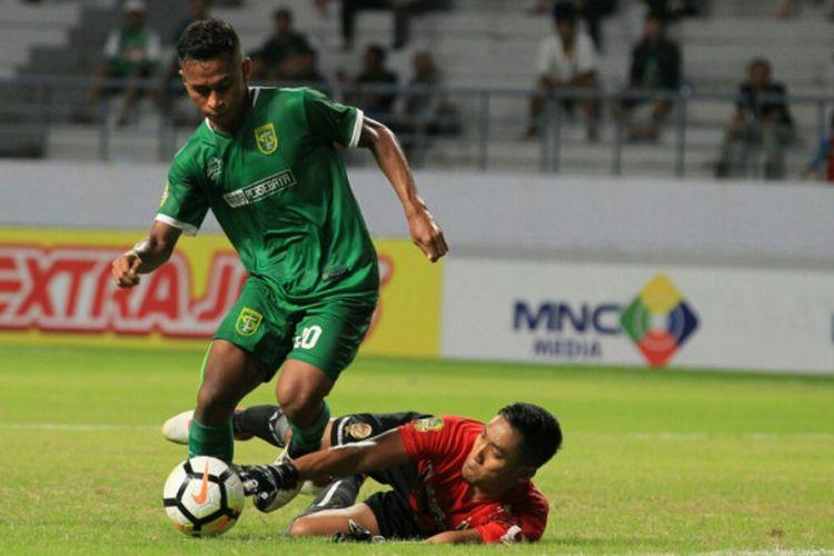 Winger Persebaya, Osvaldo Haay (kiri) merebut bola dari kiper Sriwijaya FC, Sandi Firmansyah pada laga pamungkas Grup B Piala Gubernur Kaltim 2018 di Stadion Batakan, Balikpapan, Rabu (28/2/2018) malam.