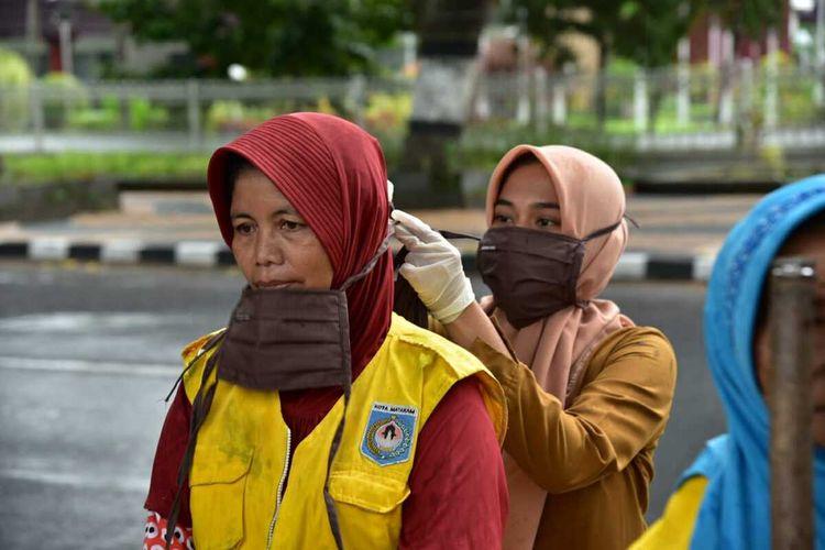 Petugas membagikan masker kain untuk warga.