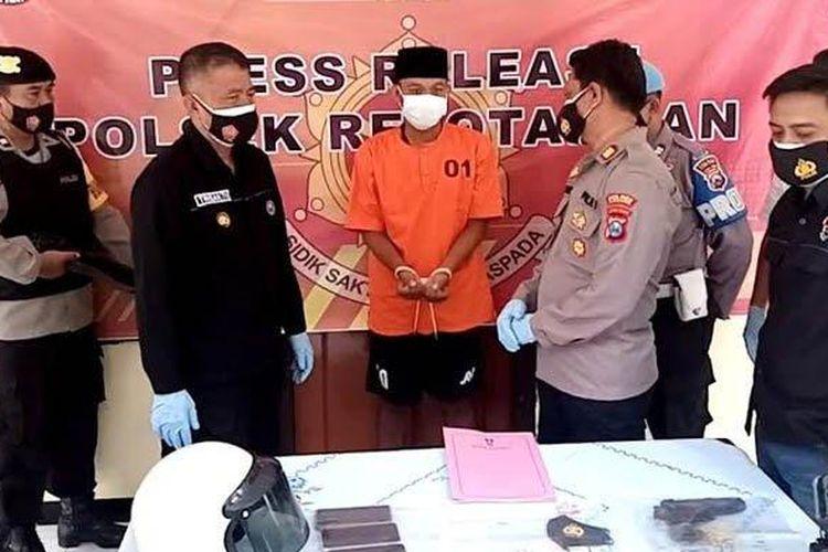 AW (24), tersangka penipuan dan penggelapan dengan modus menyaru sebagai polisi saat di Mapolsek Rejotangan, Selasa (16/3/2021).
