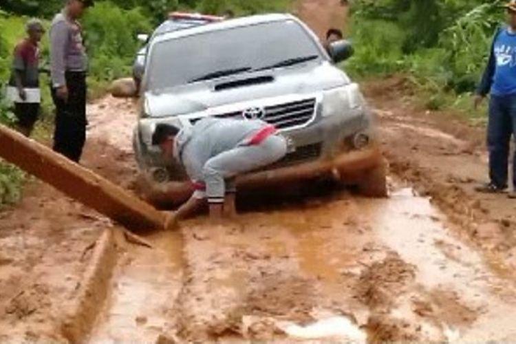 Mobil rombongan bantuan bencana tanah longsor dan banjir di Mamuju Tengah, Sulawesi Barat terjebak kubangan lumpur saat menuju lokasi bencana. Bantuan logistik yang harusnya diserahkan pagi hari baru sampai di lokasi menjelang malam hari, Minggu (17/2/2019).