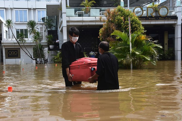 Petugas hotel membawa koper milik tamu saat banjir melanda kawasan Kemang, Jakarta Selatan, Sabtu (20/2/2021). Banjir yang terjadi akibat curah hujan tinggi serta drainase yang buruk membuat kawasan Kemang banjir setinggi 1,5 meter.