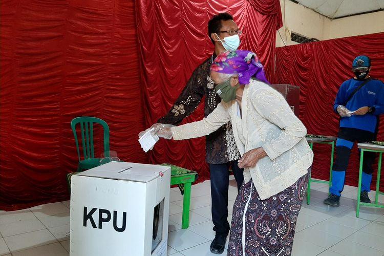 Seorang pengungsi Gunung Merapi berusia lansia warga Kalitengah Lor saat memasukan surat suara ke kota suara di TPS 8 di Dusun Banjarsari, Glagaharjo, Cangkringan, Sleman.