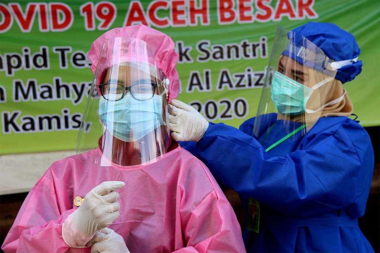 Tenaga medis dari Puskesmas dan Dinas Kesehatan Kabupaten Aceh Besar bersiap melakukan pemeriksaan tes cepat atau rapid test kepada para santri di Pesantren Mahyal Ulum Al Aziziyah di Kecamatan Suka Makmur, Kabupaten Aceh Besar, Kamis (11/6/2020). Pesantren di Aceh kembali melaksanakan aktivitas belajar mengajar setelah libur panjang terkait Covid-19 dan bulan Ramadhan dengan mengedepankan protokol kesehatan jelang era normal baru guna mencegah penyebaran Covid-19.