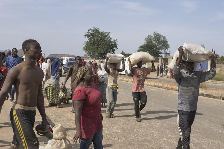 Orang-orang membawa karung-karung berisi makanan di atas kepala mereka selama penjarahan massal di gudang yang berisi bantuan makanan selama Covid-19 yang tidak diberikan selama penguncian untuk meredakan kelaparan, di Jos, Nigeria, pada 24 Oktober 2020.