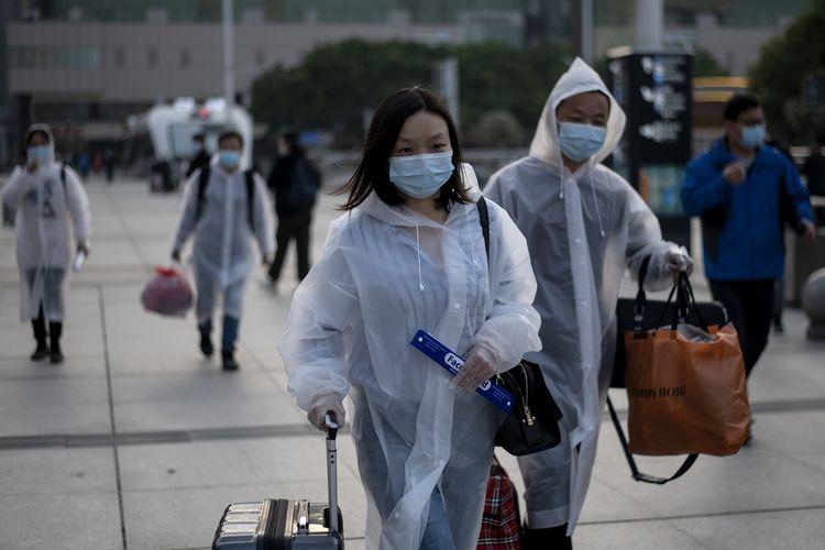 Orang-orang mengenakan masker sampai di Stasiun Kereta Hankou, Wuhan, untuk menumpang kereta pertama setelah pemerintah mencabut lockdown guna menangkal virus corona pada 8 April 2020. Sudah 76 hari warga ibu kota Hubei tersebut dikarantina demi mencegah penyebaran wabah.