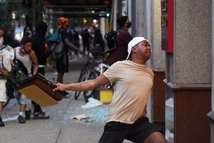 Rainey A Backues saat hendak memecahkan kaca sebuah bangunan, ketika ikut demonstrasi kematian George Floyd yang berlangsung ricuh di Philadelphia, Amerika Serikat, Senin (1/6/2020).