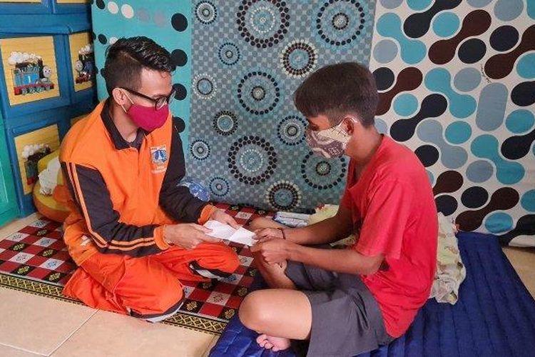 Petugas PPSU Duri Pulo, Angga memberikan donasi kepada Mulyadi, ayah Kenzi, untuk membelikan susu khusus bayi penderita epilepsi intraktabel pada Senin (12/7/2021).