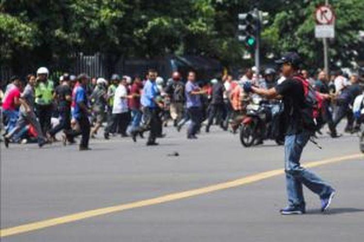 Foto ini dirilis oleh agensi berita China Xinhua, seorang pria tak dikenal dengan senjata, terduga pelaku, terlihat setelah ledakan menghantam kawasan Jalan MH Thamrin, Jakarta Pusat, 14 Januari 2016. Serangkaian ledakan menewaskan sejumlah orang, terjadi baku tembak antara polisi dan beberapa orang yang diduga pelaku.
