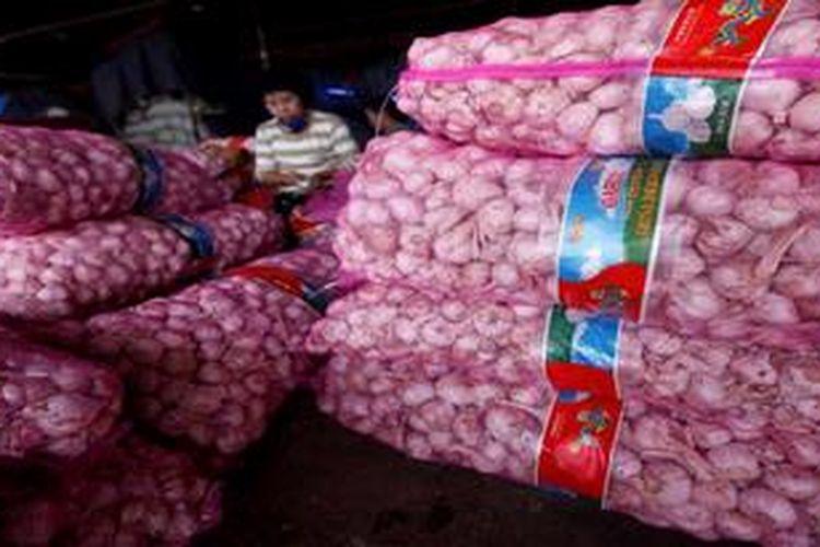 Buruh kupas bekerja mengupas Bawang Putih impor dari China di Pasar Induk Tanah Tinggi, Kota Tangerang, Banten, beberapa waktu lalu.