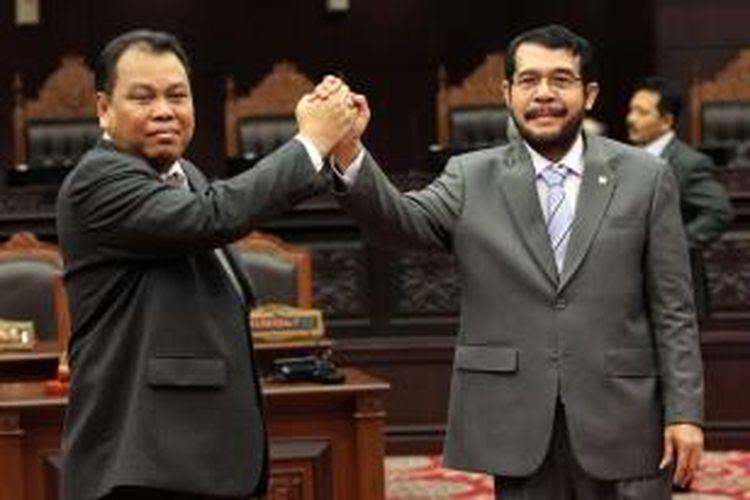 Ketua Mahkamah Konstitusi periode 2015-2017 Arief Hidayat (kiri) bersalaman dengan wakilnya yang juga baru terpilih, Anwar Usman, usai mengikuti Rapat Permusyawaratan Hakim Konstitusi di Gedung MK, Jakarta, Senin (12/1/2015).