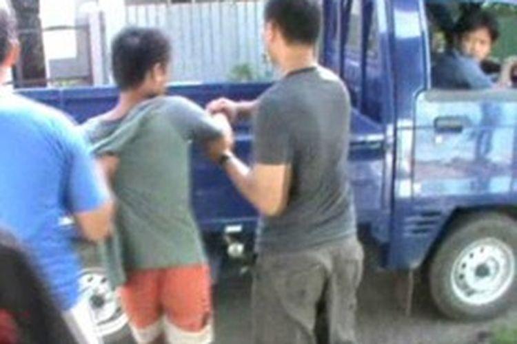 Il, salah satu pelaku pencurian barang rongsokan saat digelandang petugas dari rumahnya ke Polsek Polewali Mandar, Kamis (4/7/2013).