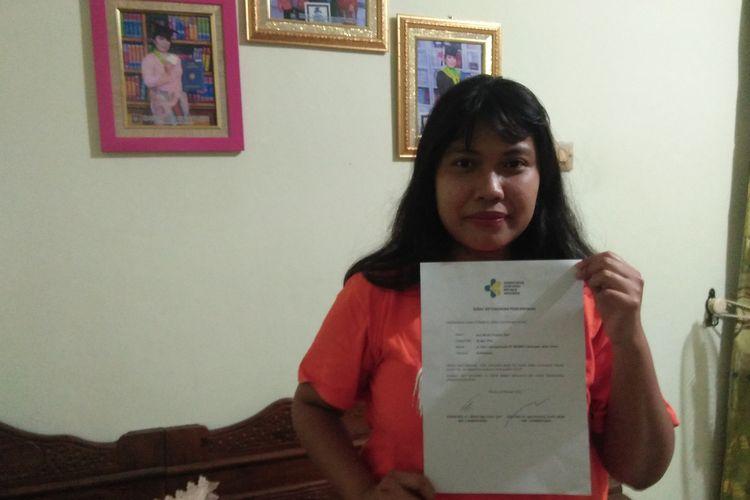 Ayu Winda Puspitasari saat menunjukkan surat kesehatan bebas dari virus corona.