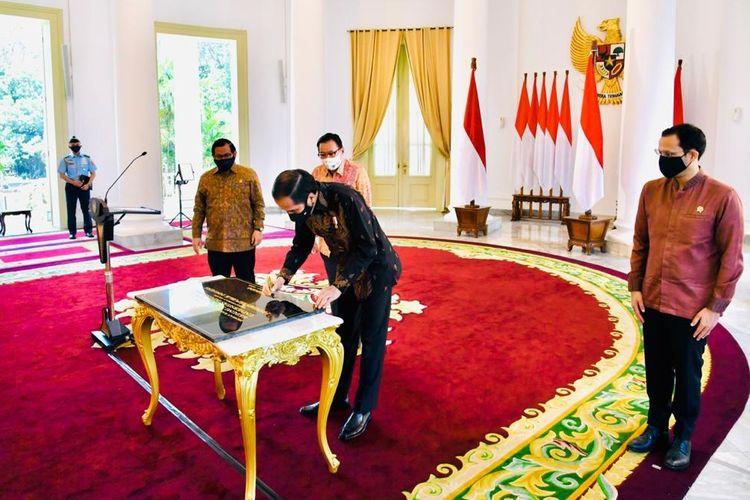 Presiden Joko Widodo menandatangani prasasti peresmian di Istana Kepresidenan Bogor, Rabu (26/8). Hadir bermasker membuat identifikasi sedikit suar, mereka adalah (dari kiri) Sekretaris Kabinet Pramono Anung, Managing Director Sinar Mas, G. Sulistiyanto serta Menteri Pendidikan dan Kebudayaan Nadiem Makarim