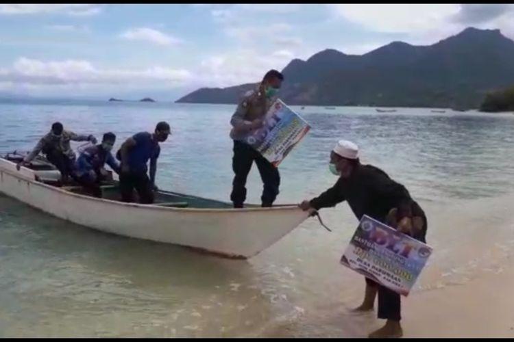 Foto : Kepala dan Aparat Desa Parumaan bersama anggota TNI dan Polri menyebrangi laut untuk membagikan BLT dana desa kepada masyarakat, Sabtu (16/5/2020).