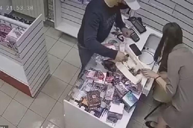 Potongan rekaman video memperlihatkan penjaga toko meraba-raba bagian bawah konternya, sebelum memukulkan mainan seks dildo ke arah perampok di Rusia, pekan lalu.