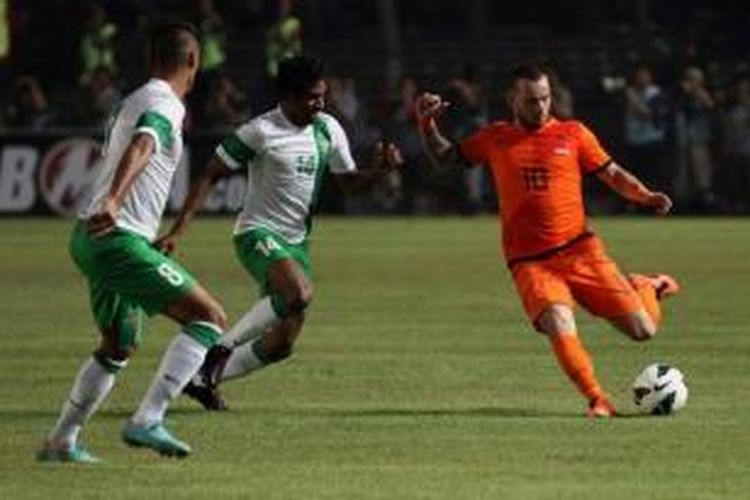 Pemain Tim Nasional Belanda Wesley Sneijder (kanan), mencoba melewati hadangan pemain belakang Timnas Indonesia di Stadion Utama Gelora Bung Karno Senayan, Jakarta, Jumat (7/6/2013).