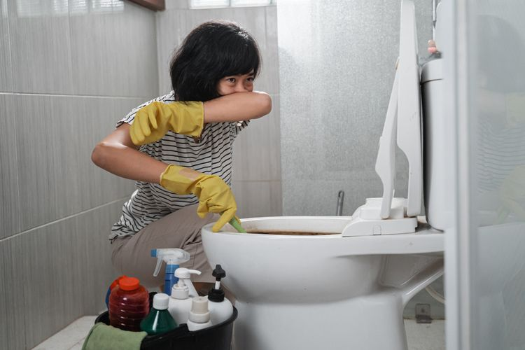 Ilustrasi membersihkan kamar mandi yang bau.