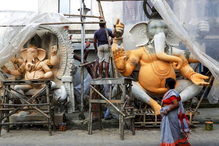 Seorang wanita berjalan melewati seorang pengrajin yang sedang mengerjakan patung dewa Hindu berkepala gajah Ganesha di sebuah studio pinggir jalan di Kolkata, India, Rabu, 8 September 2021.