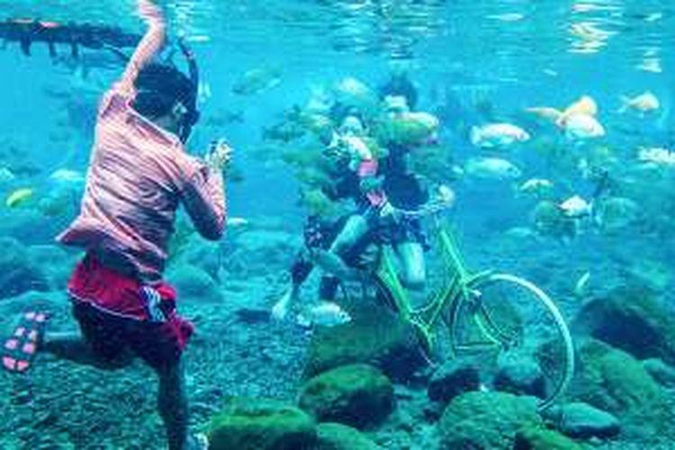 Pengunjung Umbul Ponggok di Desa Polanharjo, Kabupaten Klaten, Jawa Tengah, menyewa jasa warga setempat yang berprofesi sebagai fotografer bawah air, Minggu (14/8/2016).