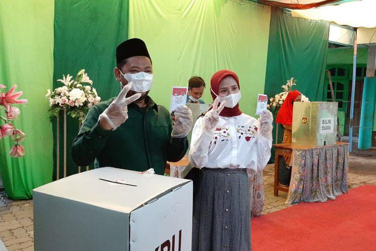 Fandi Akhmad Yani (kiri) bersama istri, saat menyalurkan hak pilihnya di TPS 02 Desa Kemudi, Rabu (9/12/2020).