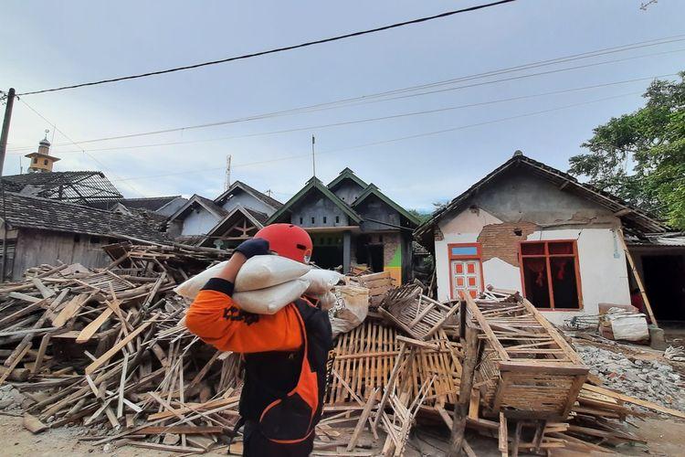 Seorang relawan mengangkut bantuan logistik untuk korban gempa di Desa Majangtengah, Kecamatan Dampit, Kabupaten Malang, Senin (12/4/2021).
