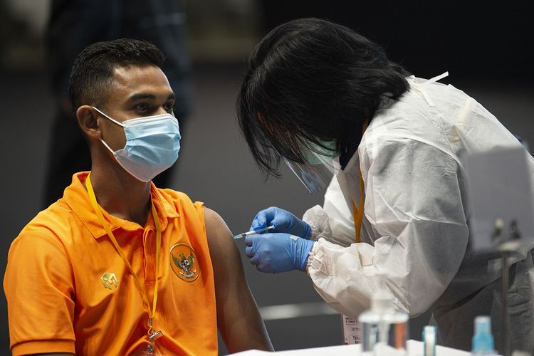 Petugas menyuntikkan vaksin COVID-19 kepada pesepak bola Timnas sepak bola U-23 Miftahul Hamdi (kiri) di Istora Senayan, Gelora Bung Karno (GBK), Jakarta, Jumat (26/2/2021). Kementerian Pemuda dan Olahraga (Kemenpora) bersama Kementerian Kesehatan (Kemenkes) melakukan vaksinasi COVID-19 perdana kepada insan olah raga nasional dengan menyasar 820 orang, termasuk atlet, pelatih dan tenaga kesehatan dari 40 cabang olahraga (cabor). ANTARA FOTO/Aditya Pradana Putra/rwa.